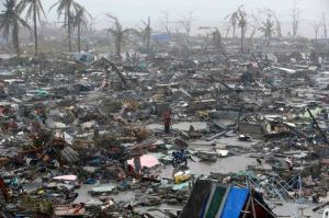People stand among debris and ruins of houses after Typhoon Haiyan pulverized the city of Tacloban.